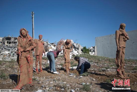 当地时间2014年10月21日,加沙,巴勒斯坦艺术家Eyad Sabbah用玻璃纤维和粘土在废墟之中展出雕像,描绘在巴以冲突中巴勒斯坦人逃离家园的状态。