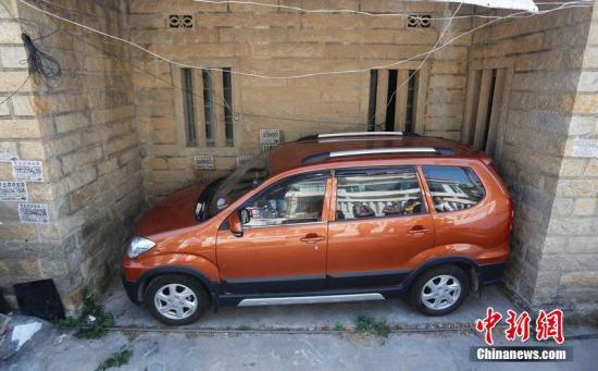 资料图:福建泉州,一部车子停在华侨新村一条巷子凹槽中,引来围观。