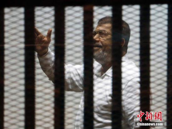 资料图:2014年11月18日,埃及开罗,埃及前总统穆尔西和其他穆兄会成员一起出庭受审。图片来源:CFP视觉中国