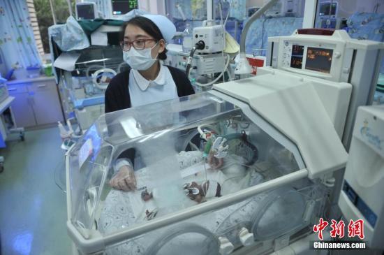 资料图:产科护士与新生儿。陈超 摄