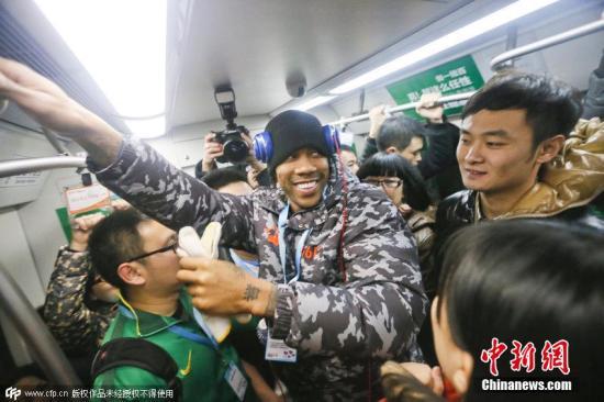 资料图:2014年马布里现身北京地铁,在车厢里,老马做起了志愿者,动手清理车厢里的小广告,同行的地铁乘客纷纷拿出手机拍照合影。 图片来源:CFP视觉中国