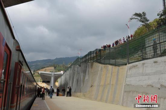 12月10日,火车在屏边站停靠时,许多民众来到火车站外看热闹。当日,云南首条联通东南亚的国际准轨铁路昆(明)河(口)准轨铁路正式开通客运,全程约6小时抵达云南河口县。河口县位于云南省东南部,与越南老街省老街市隔河相望,便捷的出境游一直受到众多旅客喜爱。中新社发 刘冉阳 摄