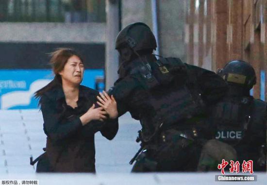 资料图:2014年悉尼咖啡馆人质劫持事件现场,女性人质从劫持现场逃跑出来。