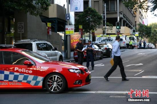 资料图:2014年12月,澳大利亚悉尼市中心CBD地区马丁广场的一咖啡店发生劫持人质事件,警方包围了这个咖啡店,控制现场,并封锁相关路段。中新社发 朱大强 摄