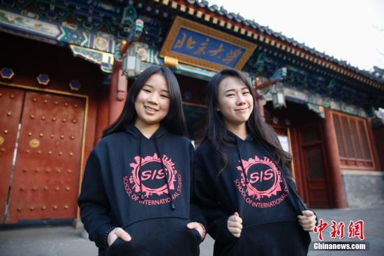 图为泰国华裔留学生李慧敏(左)和白云莹(右)在北京大学校门前身着北京大学国际关系学院校服合影。中新社发 王骏 摄