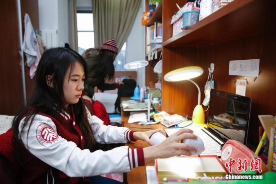 12月17日,在北京大学留学生宿舍内,泰国华裔留学生白云莹(前)与李慧敏正在收拾房间。在她们的书桌上摆满了各类汉语书籍。<a target='_blank' href='http://www.chinanews.com/'>中新社</a>发 王骏 摄