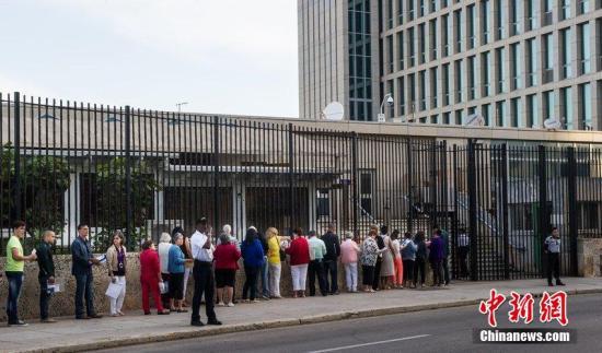 当地时间2014年12月22日,古巴哈瓦那,古巴民众在美国驻古巴首都哈瓦那办事处外排队等待申请签证。图片来源:CFP视觉中国