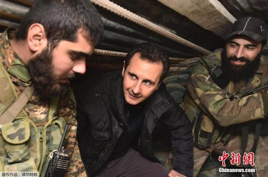当地时间2014年12月31日公布的图片,叙利亚大马士革东部Jobar地区,叙利亚总统阿萨德新年前夕慰问前线士兵,与他们亲切交流,并共进美食。