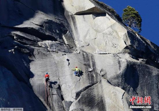 """当地时间2015年1月14日,美国加州,美国男子约根森和卡德威在经历了19天的连续攀爬后,终于成功到达号称全球最艰巨的岩石""""黎明之墙""""的顶部,成为第一个自由攀爬此岩石成功典范,创造了历史。据报道,来自美国加利福尼亚州的30岁男子约根森和科罗拉多州的36岁男子卡德威仅靠双手和双脚攀登优胜美地国家公园酋长巨石(El Capitan)。酋长巨石是全球最大的花岗岩巨型独石,耸立于优胜美地谷,高914米。约根森和卡德威吃睡都在酋长巨石""""黎明之墙""""(Dawn Wall)的悬挂帐篷解决。"""