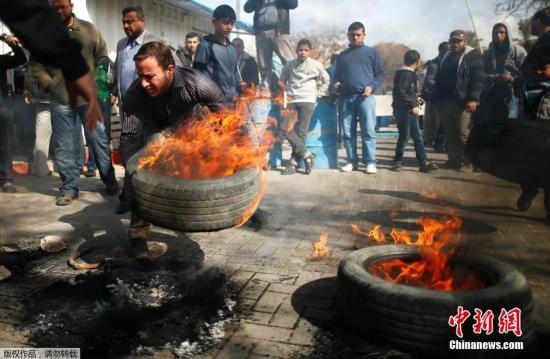 当地时间2015年1月28日,加沙地带,巴勒斯坦示威者在当地联合国总部外,焚烧轮胎,冲击联合国机构办事处,并向相关建筑投掷石块,以抗议联合国救援机构暂停支付巴勒斯坦民众修缮在去年巴以冲突中被毁房屋的费用。