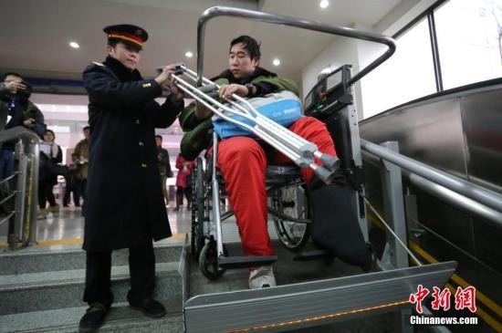 资料图:火车站工作人员帮扶残障人士通过无障碍通道进站乘车。中新社发 杨正华 摄