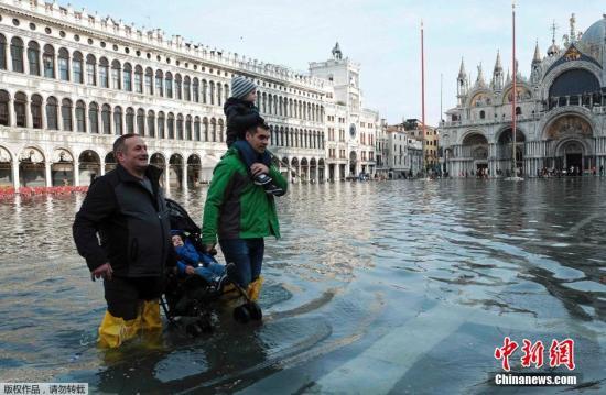 图为当地时间2月2日,意大利威尼斯的圣马可广场被水淹没,游客游兴不减穿梭期中。
