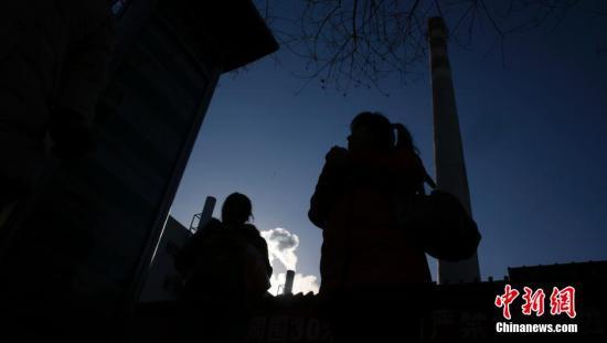 资料图:北京市区大屯路附近,一根高耸的燃煤烟囱已停止了使用,取而代之的是旁边燃烧天然气的小烟囱。中新社发 刘关关 摄