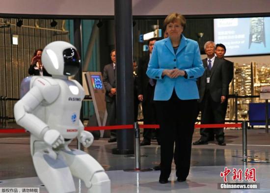 默克尔访日与机器人握手 与研究员交流科技合作