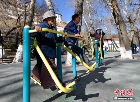 资料图:老人和孩童们在健身乐园里用各式健身器材锻炼。李林 摄