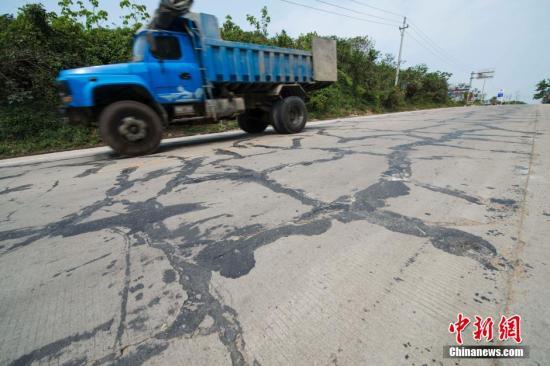 """3月13日,一辆重型卡车正在海榆西线铺仔、西培一带路段的""""纹身""""公路上行驶。中新社发 骆云飞 摄"""