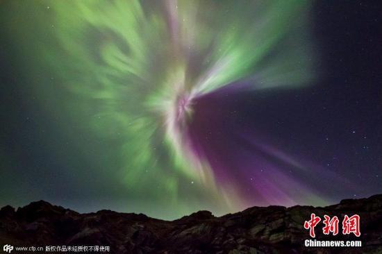 资料图:2015年,苏格兰北部海岸的萨瑟兰郡上空,出现了梦幻般的粉色极光。据悉,这种罕见的粉色极光美景是由于近期大规模的太阳风暴造成的。据NASA官员17日表示,上周末两次太阳爆发现象引发强烈磁暴,为当前太阳周期最强大的太阳风暴。 图片来源:CFP视觉中国