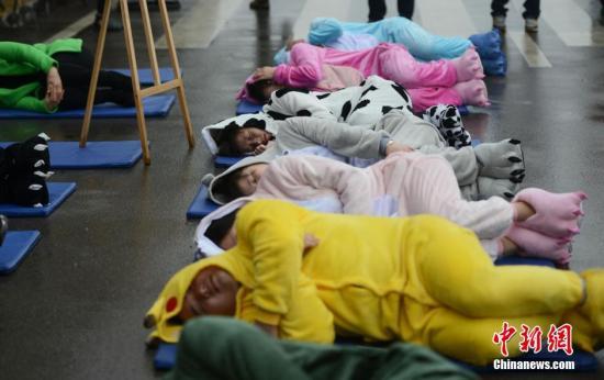 """3月20日,世界睡眠日前夕,被誉为中国""""睡眠先生""""的唐堂带领众多市民来到长沙街头进行""""睡大街""""公益行为艺术展示,呼吁市民提高深度睡眠质量,远离肥胖与亚健康。唐堂表示,深度睡眠是最好的化妆品,既美容又减肥。 杨华峰 摄"""