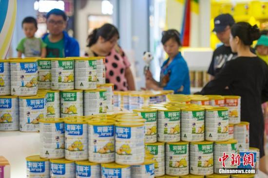 图为游客在海南三亚海棠湾免税购物中心选购免税奶粉。<a target=
