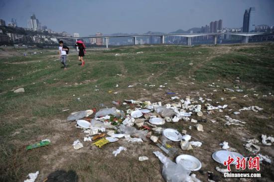 3月25日,长江重庆段裸露河床堆放着不少白色塑料垃圾。长江水位下降,大片河床裸露在外,成了市民休闲娱乐地。不少市民在此进行野外烧烤,留下了不少垃圾在河床上。陈超 摄