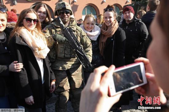 当地时间2015年3月24日,波兰比亚韦斯托克,美国士兵与当地居民在当地市集广场合影。美国士兵从爱沙尼亚返回其在德国巴伐利亚州的基地。