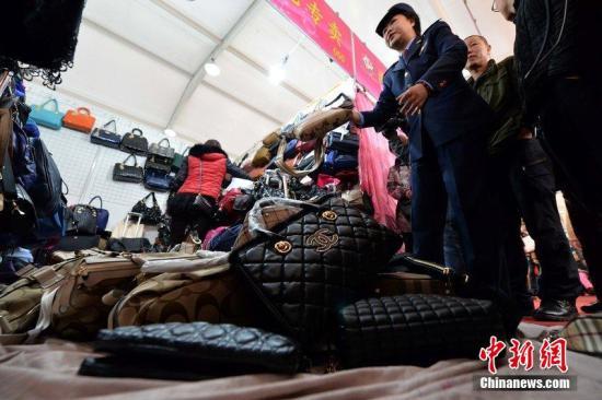 3月25日,北京,工商人员查出涉嫌出售假名牌包的摊位,将假货没收。 徐晓帆 摄 图片来源:CFP视觉中国