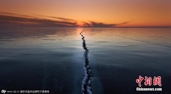 2015年4月1日消息,俄罗斯贝加尔湖面结冰,数百米长的裂缝仿佛将世界一分为二,夕阳的余晖洒在湖面上景色神奇迷人。图片来源:CFP视觉中国