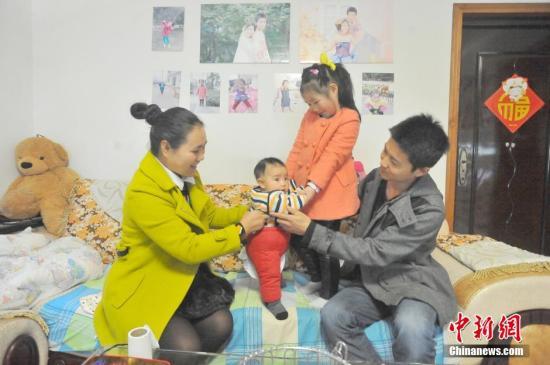 """资料图:湖北宜昌多个""""单独二孩""""家庭拍摄全家福,在镜头前秀幸福。"""