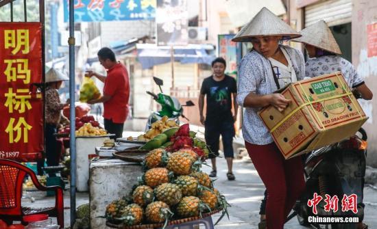 """4月3日,一位越南商贩在云南省河口市中越边境附近卸下水果,这个摊位写着""""明码标价""""的广告。发 张浩 摄"""