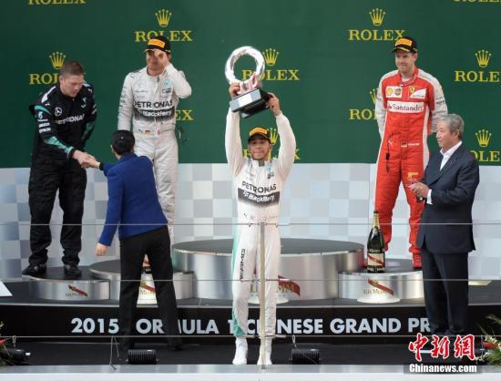 4月12日,世界一级方程式赛车(F1)锦标赛在上海赛车场举行,梅赛德斯AMG车队的英国车手路易斯·汉密尔顿(中)夺得冠军。图为颁奖仪式。<a target='_blank' href='http://www.chinanews.com/'>中新社</a>发 侯宇 摄