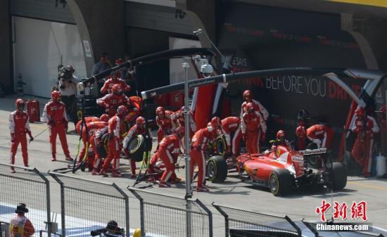 4月12日,世界一級方程式賽車(F1)錦標賽在上海賽車場舉行,梅賽德斯AMG車隊的英國車手路易斯·漢密爾頓奪得冠軍。圖為法拉利車隊進站換胎。中新社發 侯宇 攝