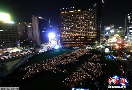 """当地时间2015年4月17日,韩国首尔,4160名手举蜡烛的民众在首尔广场组成""""世越号""""船体的形状,纪念""""世越号""""客轮沉没一周年,并向由最多蜡烛构成的物体形象方面的吉尼斯纪录发起冲击。"""