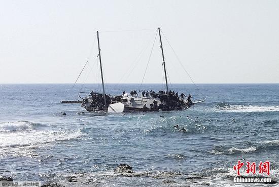 """因为偷渡船只常常""""有来无回"""",因而""""蛇头""""偏向于接纳陈旧的船只,常常更简单激发海易。图为本地工夫4月20日,希腊罗得岛四周海疆一艘不法移平易近船发作颠覆,船上灾黎试图泅水抵达岸边。"""