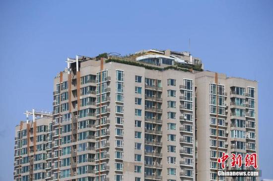"""4月22日,曾经引起轰动的北京""""最牛违建""""人济山庄B座楼顶边缘最近又被种上了灌木。记者在现场看到,B座楼顶东南角被灌木镶了一层""""绿边""""。同时,楼顶有几名工人正在施工。人济山庄物业工作人员告诉记者,他们对于楼顶发生的一切并不了解。2013年8月,在人济山庄B座楼顶上盘踞了6年的违法建筑""""空中别墅""""被媒体曝光。违建内有台球厅、KTV房、游泳池,甚至有自带的电梯。要想到达""""空中别墅"""",只能从业主张必清家内部进入。在被曝光之后,张必清自行拆除了屋顶违建。图片来源:CFP视觉中国"""