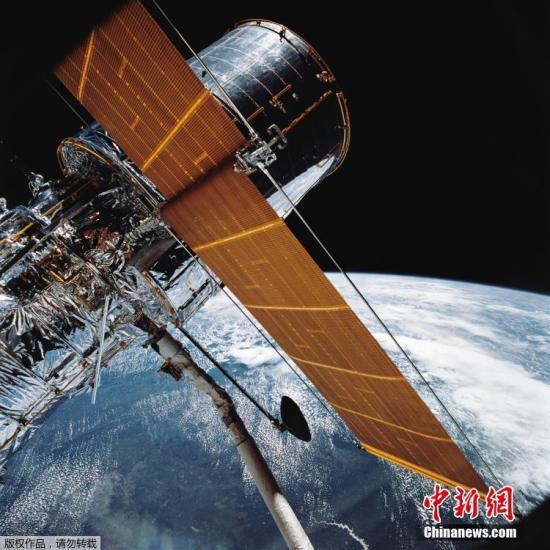 """资料图:1990年4月24日,美国航天飞将哈勃望远镜送上太空轨道,""""哈勃""""望远镜长13.3米,它以2.8万公里的时速沿太空轨道运行,由于没有大气湍流的干扰,它所获得的图像和光谱具有极高的稳定性和可重复性。至今,哈勃太空望远镜已经环绕地球飞行25年,它捕捉到的照片正从根本上改变着我们对宇宙的认识。"""