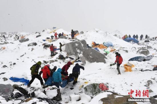 当地时间4月25日,尼泊尔强震引发珠穆朗玛峰雪崩,部分基地大本营被埋。救援队紧急救援。