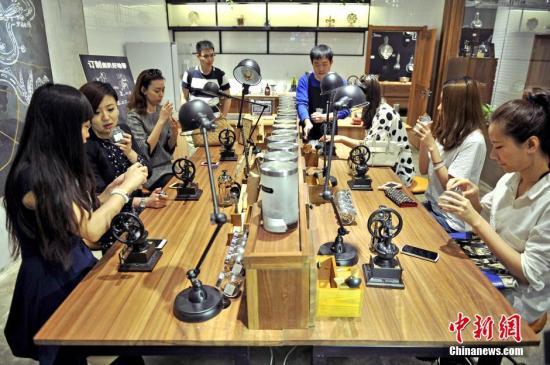 """4月27日,顾客在""""良食局""""内体验自制咖啡。当天,中国第一家购物中心O2O情景式会员体验中心""""良食局""""在天津大悦城启幕。作为天津大悦城APP中的会员线下实体店,良食局将完成O2O积分消费模式,并通过一系列增值服务,将其打造成为线上线下立体化会员体验平台。顾客可以在店铺内的""""粮仓""""区体验打粮、装粮的乐趣,""""咖啡先生""""区可以自己动手做咖啡,""""等你来掌勺""""的厨房区可以自己动手为朋友们做饭等。<a target='_blank' href='http://www.chinanews.com/'>中新社</a>发 佟郁 摄"""