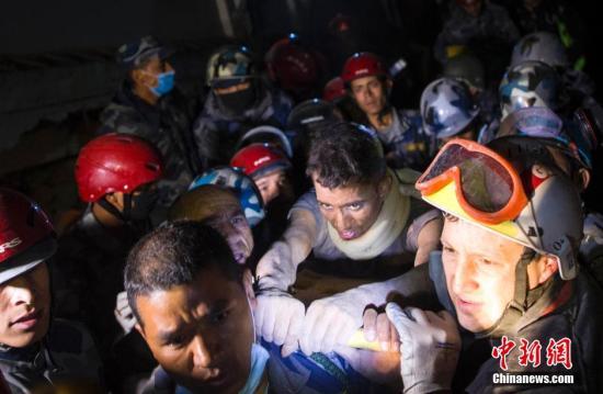 4月29日凌晨0点29分,一名20岁的尼泊尔男子在法国救援队的努力下从加德满都的一座楼房中脱险,在地震发生82小时后生还。图为他上救护车后接受医生检查。 <a target='_blank' href='http://www.chinanews.com/'>中新社</a>发 张浩 摄