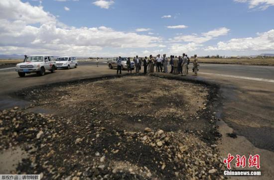 资料图:当地时间2015年5月5日,也门萨那,也门机场人员正在检查由沙特主导的空袭中被炸毁的国际机场的跑道。