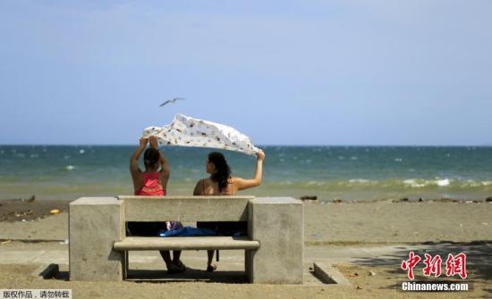 资料图片:游客在哥斯达黎加卡尔德拉海滩下海游泳玩耍。