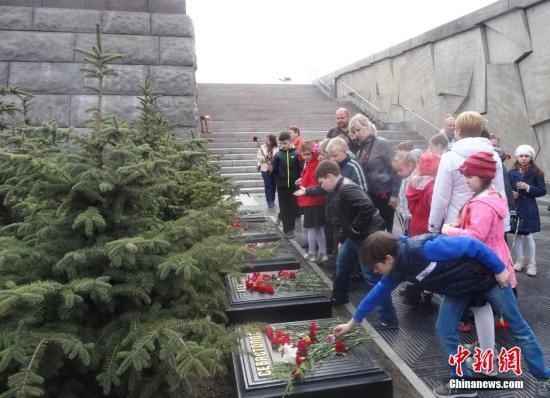 """5月7日,俄罗斯圣彼得堡二战胜利广场。俄罗斯少年儿童向二战""""英雄城市""""纪念物献花。 中新社发 田冰 摄"""