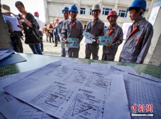 建筑用工企业展示为农民工发放工资的银行小票及缴纳工伤保险的复印件。刘新 摄
