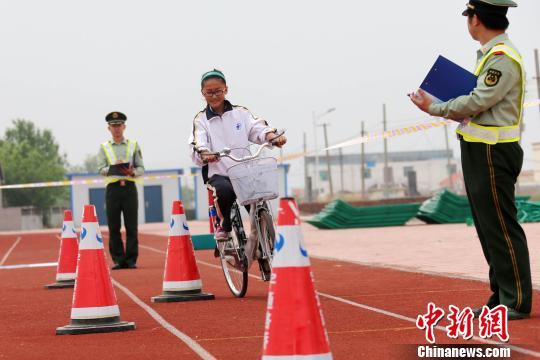 资料图:山东东营东海边防派出所民警为辖区内滨海学校12岁以上学生组织了一场趣味自行车骑行考试。。梁�� 摄