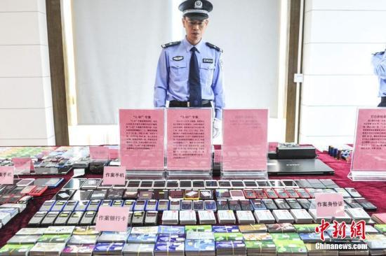 资料图:警方展示电信诈骗作案工具。中新社发 陈骥�F 摄