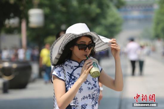 5月25日,北京高温,行人在北京前门大街行走。 中新社发 熊然 摄