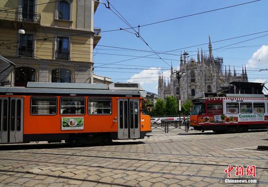 """图为当地时间5月27日,意大利米兰,两辆有轨电车在米兰的地标性建筑米兰大教堂广场前""""擦肩而过""""❘◘。 中新网记者 李卿 摄"""