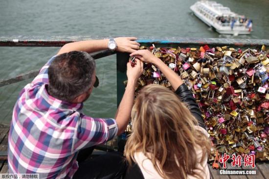 """当地时间2015年5月29日,法国巴黎,艺术桥桥挂满爱情锁。巴黎艺术桥位于塞纳河畔,始建于1804年,在两次世界大战期间遭到德军轰炸被毁,最终在上个世纪80年代得以重建。来到这里的游客,在把锁固定在桥上后,会将钥匙扔河里表示""""忠心""""。欧洲人在桥上拴锁的传统始于20世纪初,以纪念在战争中阵亡的情人,人们将这个传统保持至今。所以该桥也称:爱情锁桥。现在,很多桥梁因此不堪重负,存在重大安全隐患。由于挂锁的人太多,而桥上空间有限,为了能把自己的锁放上去,很多人开始变得异常疯狂,他们往往要冒着危险爬到更高的地方,或者探身到水面上才能完成""""任务""""。2014年6月,爱情锁桥部分桥段因不堪重负倒塌。"""