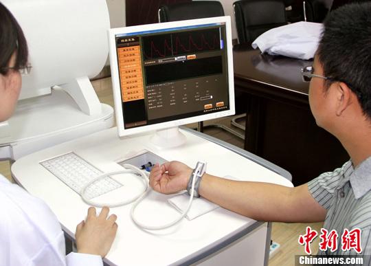 5月28日,天津大学精仪学院中医工程实验室在用最新研发的智能中医综合诊断系统对病人进行诊治。中新社发 张道正 摄