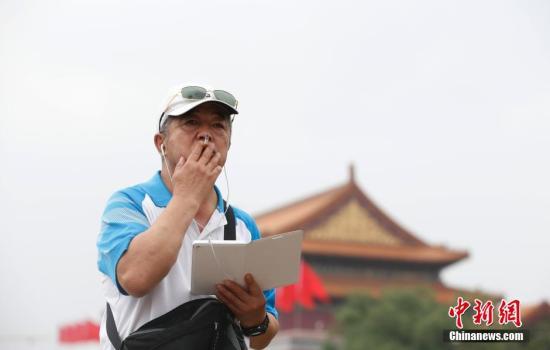 """6月1日,一名游客在天安门城楼附近抽烟。当日,被称为""""史上最严""""的控烟条例――《北京市控制吸烟条例》正式实施。未来3天,北京卫生监督部门将重点检查党政机关、医疗机构、学校、宾馆、饭店、娱乐场所;6至8月将进行集中行政处罚,并将在每个月确定一周为全市集中行政处罚周。根据《条例》,场所的经营者、管理者违反条例,处2000元以上1万元以下罚款;个人在禁止吸烟场所或者排队等候队伍中吸烟的,罚款50元或200元。&#xA;<a target='_blank' href='http://www-chinanews-com.admin987.com/'>中新社</a>发 刘关关 摄"""