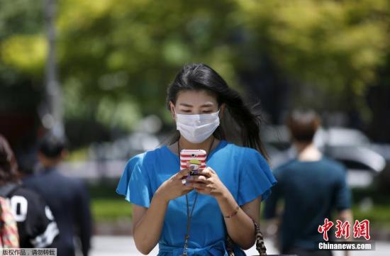 6月3日,在韩国首尔市中心的商业区,游客戴口罩出行。